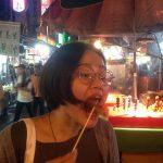 Rocío comiendo en la calle en el mercado nocturno de Guanzhou